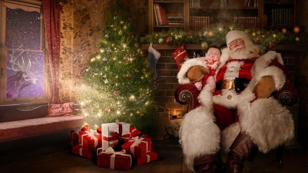 Ein kleines Mädchen sitzt auf dem Schoß eines Weihnachtsmanns