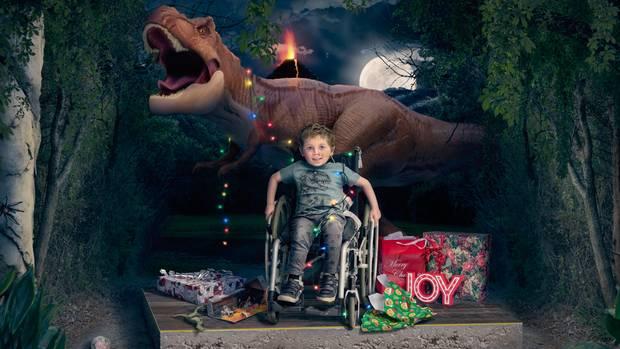 Ein kleiner Junge sitzt vor einem Dinosaurier