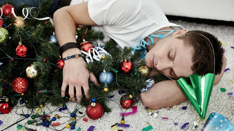 Mann schläft neben Weihnachtsbaum
