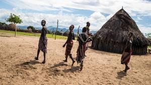 Mehrer Bewohner gehen in traditioneller Kleidung durch ein Hüttendorf in Äthiopien