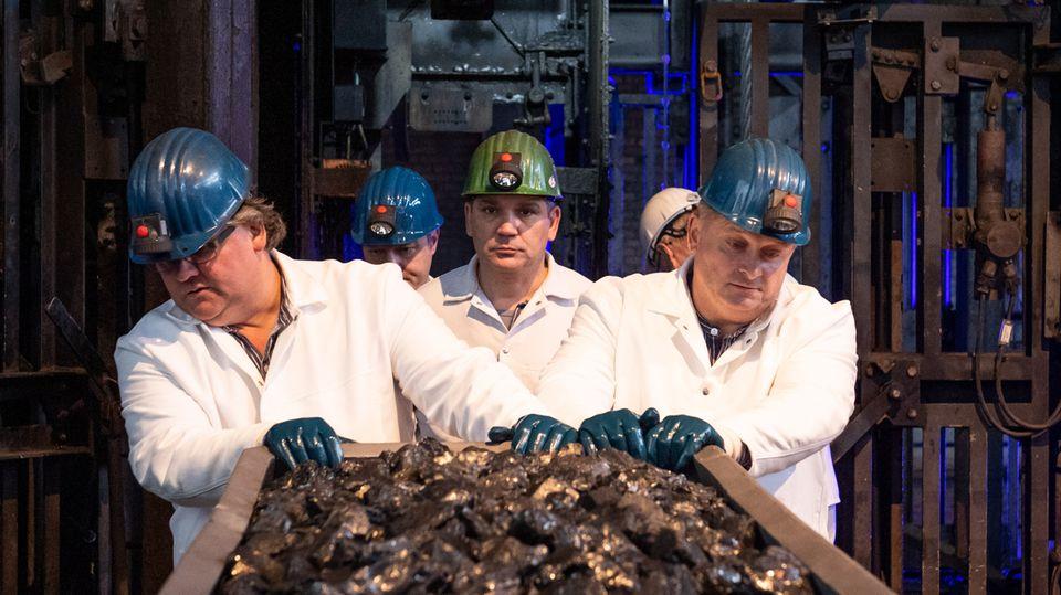 Drei Männer mit Grubenhelmen und weißen Kitteln schieben eine Lore aus der Zeche Ibbenbüren
