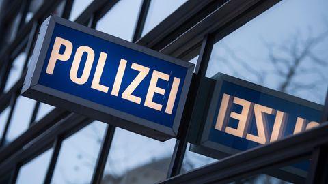 """In den Scheiben einer Polizeiwache spiegelt sich ein """"Polizei""""-Leuchtschild"""