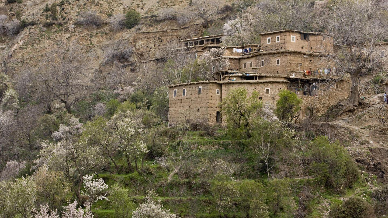 Quadratische Steinhäuser stehen an einem Hang mit künstlich angelegten Terrassen