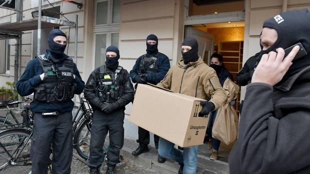 Vermummte Ermittler tragen unter Schutz des SEK Kartons und Tüten aus einer Moschee in Berlin-Wedding