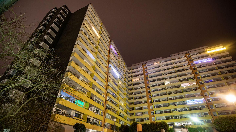 Im Dunkeln ragt das L-förmige Hochhaus in Heidelberg in die Höhe, viele Fenster sind dunkel, aus anderen scheint Licht