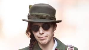 Eine Frau in grüner Lodentracht, Hut und Sonnenbrille geht einen Fußweg entlang