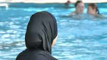 Eine Frau sitzt in einem Burkini am Rande eines Schwimmbeckens