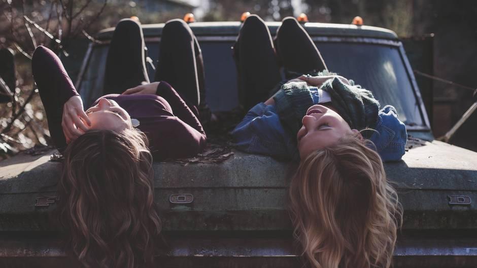 Zwei Freundinnen liegen auf einem Auto