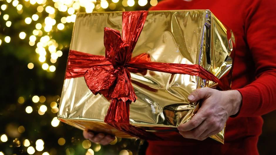 Ein Mann hält ein goldenes Paket