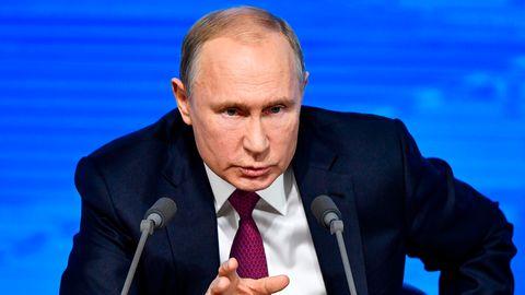 Russlands Präsident Wladimir Putin sitzt hinter zwei Mikros und vor einer blauen Wand während einer Pressekonferenz