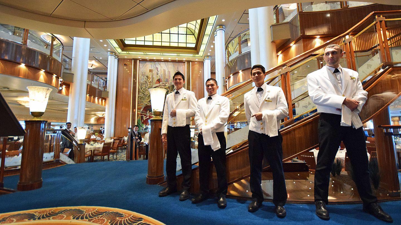 Hartes Arbeitspensum, wenig Lohn: Servicekräfte am Eingang zum Hauptrestaurant eines Kreuzfahrtschiffes