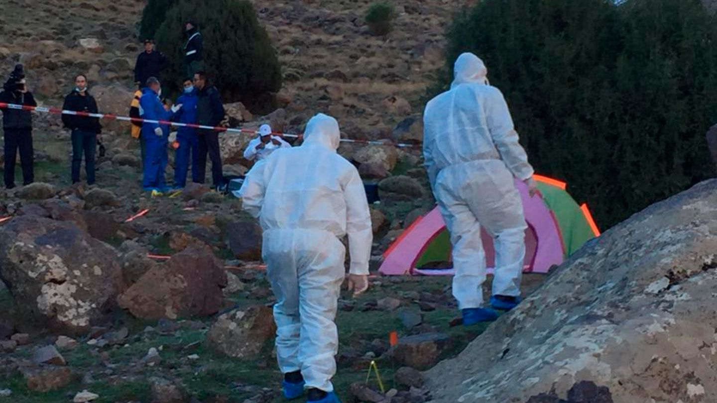 Zwei Menschen in weißen Overalls nähern sich einem bunten Zelt, das zwischen Felsen steht