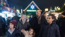 Eine fünfköpfige Familie geht über einen Weihnachtsmarkt. Die Augen der Kinder leuchten, ein kleines Mädchen zeigt auf etwas
