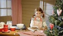 Ein kleines Mädchen backt Weihnachtsplätzchen