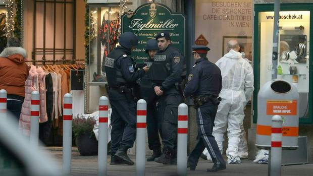 Nach den Schüssen in Wien sichern schwer bewaffnete Polizisten den Tatort