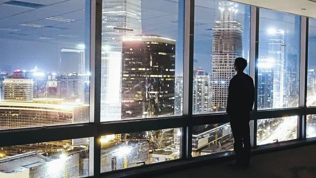 Ein Mann blickt auf die abendlich erleuchteten Wolkenkratzer in Peking. Wie die Hauptstadt haben sich alle größeren Städte Chinas in nur wenigen Jahren zu glitzernden modernen Metropolen entwickelt.