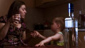 Ein Frau trinkt Alkohol im Beisein ihres kleinen Kindes