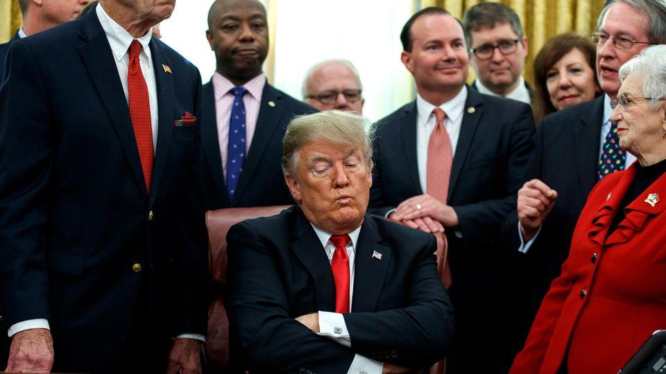 US-Präsident Donald Trump sitzt mit verschränkten Armen an einem Schreibtisch und schaut verkniffen