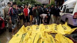 Eine Gruppe Männer steht vor etwa zwölf knallgelben Leichensäcken, in denen Todesopfer des Tsunamis liegen