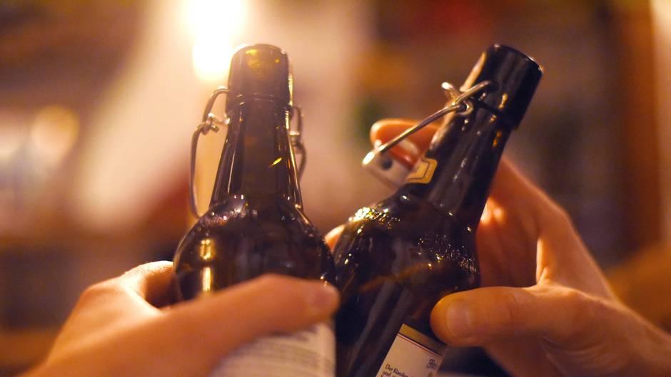 Zwei Hände stoßen mit zwei 0,5 Liter Bierflaschen an