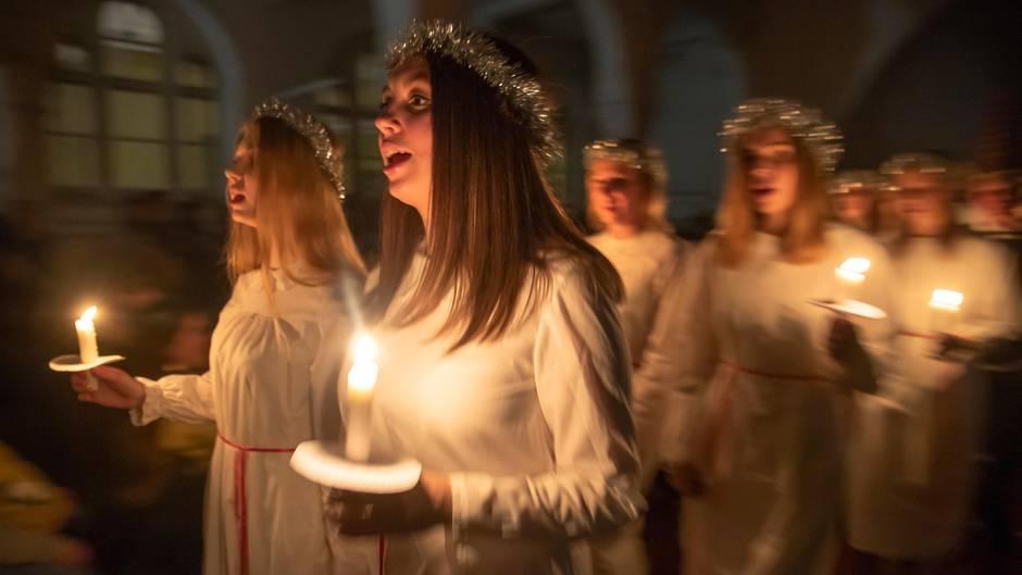 Junge Frauen in weißen Gewändern und mit Flitterkronen halten Kerzen und singen