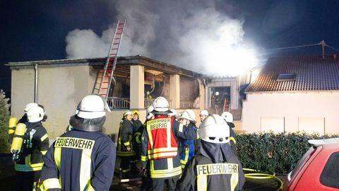 Feuerwehrleute stehen vor einem brennenden Wohnhaus in Freudenburg.