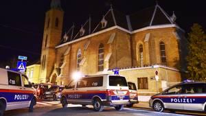 Mehrere Polizeiwagen stehen vor der Backsteinkirche Maria Immaculata in Wien-Floridsdorf