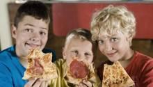 Drei Jungen mit Pizzastücken in der Hand
