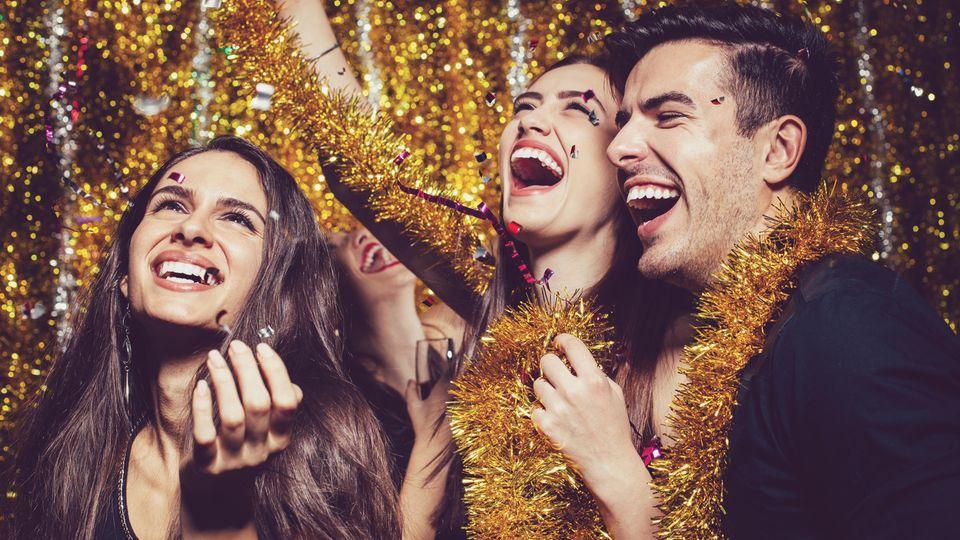 Drei junge Menschen feiern auf einer Glitzer-Party