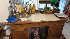 Ein Schreibtisch mit Kujaus Fälscherutensilien: Hinten links steht ein hoher Mixer zum Anrühren von Tinte,Rezeptur nach Gusto mit schwarzer und blauer Pelikan-Tinte (ebenfalls links auf dem Schreibtisch). Kujau musste immer andere Tintenfarben benutzen, damit die Tagebücher authentischer aussahen - als wären sie über Jahre hinweg geschrieben worden. Der Mixer stammt aus den 50er Jahren, er ist das einzige Modell, dasvorne einen Ausgusshatte. Davor wurde einGlas gestellt, in das die angemischte Tinte hineinlief und in das dann die Schreibfeder eingetaucht wurde. Kujau verwendete eine Stahlfeder in einem Federhalter.  Um die Tagebuchseiten alt aussehen zu lassen, hat Kujau das Papier mit schwarzem Tee vergilbt und dann mit dem Bügeleisengebügelt, damit das Papier schön glatt ist.  Der Schreibtisch selbst gehörte nicht Kujau.