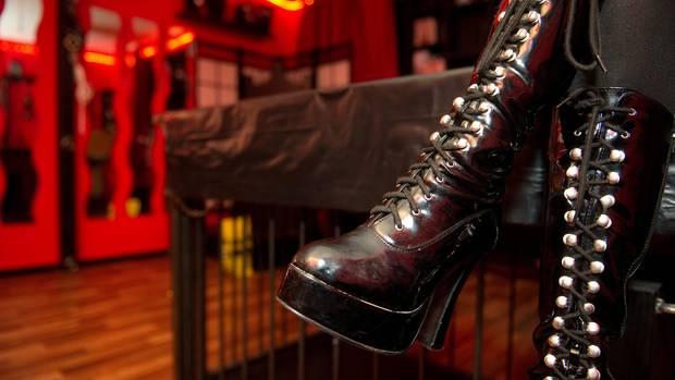 In einem rot beleuchteten Raum sind die hochhackigen, schwarzen Schnürstiefel einer Domina zu sehen
