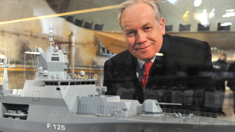 Ein Mann mit weißem Seitenscheitel lächelt durch einen Glaskasten mit dem Modell einer Fregatte hindurch