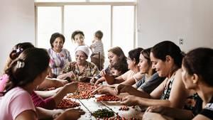 An einem großen Holztisch sitzen Frauen, sortieren Beeren und diskutieren dabei