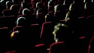 Menschen, die in einem dunklen Kinosaal sitzen