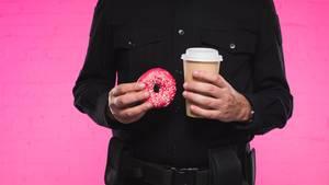 Ein us-amerikanischer Polizist mit Donuts und Kaffee