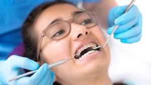 Zahnspangen: Ein junges Mädchen während einer Behandlung beim Kieferorthopäden