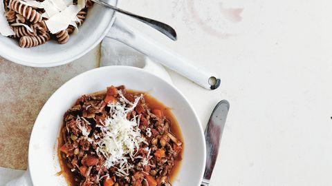 Pasta Bolognese  Zutaten:  Olivenölspray, 250 g mageres Rinderhackfleisch, 1 Zwiebel, gehackt, 1 Möhre, gehackt, 1 Knoblauchzehe, fein gehackt, 2 Dosen (à 400 g) gewürfelte Tomaten, Salz und frisch gemahlener schwarzer Pfeffer, 100 g grüne Linsen, 80 g Vollkornpasta, 1 Tomate, in Spalten geschnitten, 1 Esslöffel Olivenöl, frisch gepresster Saft von ½ Zitrone, 2 Esslöffel frisch geriebener Parmesan, 80 g Knollensellerie, geschält und gerieben      Zubereitung:  Eine tiefe Pfanne mit etwas Olivenöl einsprühen und bei mittlerer bis hoher Hitze erwärmen. Rinderhackfleisch, Zwiebel, Möhre sowie Knoblauch zugeben und 6 –8 Minuten garen, bis das Fleisch gebräunt ist; dabei häufig umrühren. Tomaten und Saft (aus der Dose) zugeben und aufkochen. Die Hitze stark reduzieren und die Sauce ohne Deckel 20 Minuten oder länger kochen, bis sie eindickt; mit etwas Salz und Pfeffer würzen.      In der Zwischenzeit Wasser in einem Topf bei mittlerer bis hoher Hitze zum Kochen bringen. Die Linsen darin 12–14 Minuten kochen, bis sie gerade weich sind; mit etwas Salz und Pfeffer würzen.      In einem zweiten Topf Salzwasser bei hoher Hitze zum Kochen bringen. Die Pasta in das Wasser geben und nach Packungsanweisung al dente kochen; dann abgießen und kurz abbrausen.      Linsen, Tomate, Olivenöl und Zitronensaft mit 1 Prise Salz in einer kleinen Schüssel verrühren.      Die Fleischsauce über die Pasta geben, Parmesan sowie Knollensellerie darüberstreuen und mit dem Linsensalat als Beilage servieren. Alternativ die Linsenmischung in die Fleischsauce rühren.