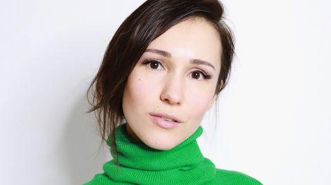 Eine junge Frau in einem knallgrünen Rollkragenpullover