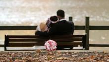 Ein Hochzeitspaar sitzt auf einer Bank