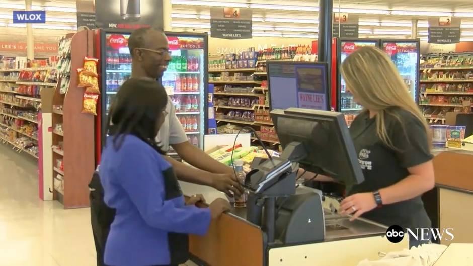 Das Ehepaar steht am Fließband der Kassiererin im Supermarkt