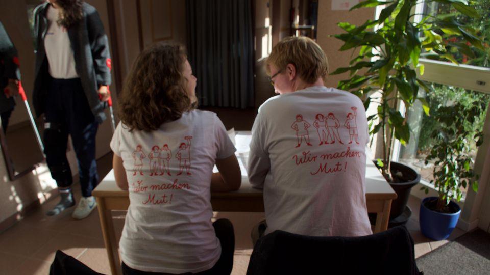 """Alle Betreuer tragen weiße T-shirts mit der Aufschrift: """"Wir machen Mut""""."""