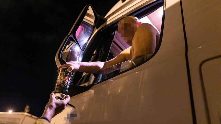 Ein Lkw-Fahrer, dem ein Bier gereicht wird