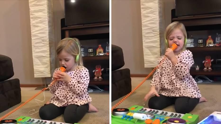 Ein kleines Mädchen hockt vor einer bunten Karaoke-Maschine und schreit in ihr Mikrofon