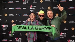 """Die drei Mitglieder von """"Fettes Brot"""" posieren mit einem grünen Schal mit """"Viva la Bernie""""-Schriftzug"""