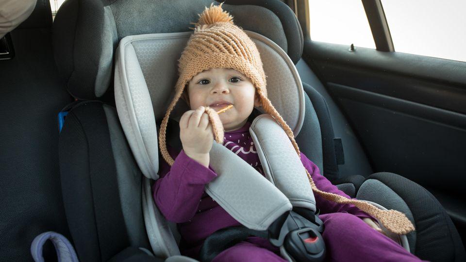 Ein Kleinkind sitzt in einem Kindersitz im Auto