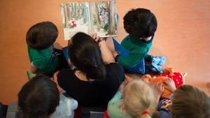 Eine Kita-Mitarbeiterin liest Kindern ein Buch vor