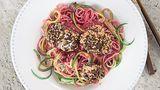 Zoodles in Rote-Bete-Pesto mit Hähnchennuggets      Zutaten:  Für das Rote-Bete-Pesto: 2 kleine frische Knollen Rote Bete (à ca. 75 g), Salz, 10 g Pinienkerne, 1 Knoblauchzehe, 15 g Parmesan, ½ unbehandelte Orange, 1–2 EL Olivenöl, frisch gemahlener schwarzer Pfeffer  Für die Zoodles: 1 große Zucchini, 100 g Dinkel-Spaghetti, Salz  Für die Hähnchennuggets: 1 Hähnchenfilet (ca. 150 g), Salz,frisch gemahlener schwarzer Pfeffer, 1 kleines Ei (Größe S), 1 EL Dinkelmehl Type 1050, 1 Scheibe Pumpernickel (ca. 42 g),1 TL Sesamsamen,1 EL Olivenöl zum Braten      Zubereitung:  Für das Rote-Bete-Pesto die Rote Bete in kochendem Salzwasser in etwa  50 Minuten weich garen. Abgießen, etwas abkühlen lassen und grob würfeln.  Die Pinienkerne in einer kleinen beschichteten Pfanne ohne Fett  goldgelb anrösten, herausnehmen und auskühlen lassen. Den Knoblauch  abziehen und grob hacken. Den Parmesan ebenfalls grob hacken.  Die Orange fein abreiben, 4–5 EL Saft auspressen, beides mit der Roten  Bete, den Pinienkernen, dem Knoblauch, dem Parmesan und dem Olivenöl  in einen hohen Rührbecher geben und mit dem Mixstab fein pürieren. Das  Pesto mit dem Salz und dem Pfeffer abschmecken.  Für die Zoodles die Zucchini waschen und mit einem Spiralschneider zu  Zucchini-Spaghetti schneiden. Die Dinkel-Spaghetti in reichlich kochendem  Salzwasser bissfest garen. Etwa 2 Minuten vor Ende der Garzeit Zucchini-  Spaghetti zugeben und mitgaren.  Für die Hähnchennuggets das Hähnchenfilet waschen, trockentupfen,  in große Würfel schneiden und mit Salz und Pfeffer würzen. Das Ei in  einem tiefen Teller mit einer Gabel verquirlen. Das Dinkelmehl auf einem  flachen Teller verteilen. Das Pumpernickel grob zerbröseln und dann im  Blitzhacker feiner mahlen. Die Brösel mit dem Sesam mischen und auf  einem flachen Teller verteilen. Die Hähnchenwürfel zuerst in dem Mehl  wenden, dann durch das Ei ziehen und zuletzt mit der Pumpernickel-  Sesam-Mischung panieren.  Das Olivenöl in einer Pfanne erhitzen und die Häh