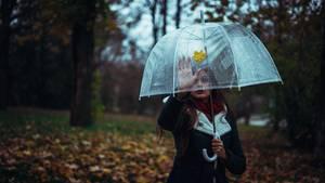 Ein Mädchen mit einem Regenschirm in Park