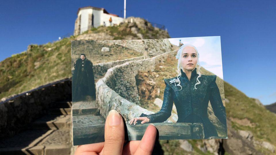 """San Juan de Gaztelugatxe in Spanien: Filmtouristin Andrea David hält ein Foto mit einer Szene aus der Serie """"Game of Thrones"""" (HBO) in die Kamera. Im Hintergrund ist der Original-Drehort zu sehen."""