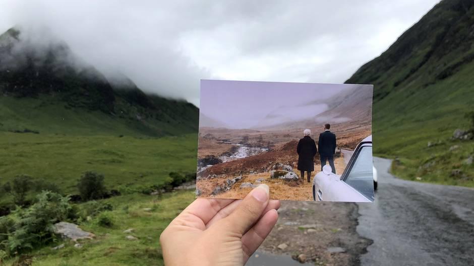 """Glen Coe in Schottland: Filmtouristin Andrea David hält ein Foto mit einer Szene aus dem Film """"James Bond 007: Skyfall"""" (Sony Pictures) in die Kamera. Im Hintergrund ist der Original-Drehort zu sehen."""